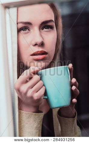 Woman looking through window in bed weather. She is pensive and lonely.