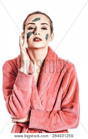 Woman applying face mask from green clay, isolated on white.