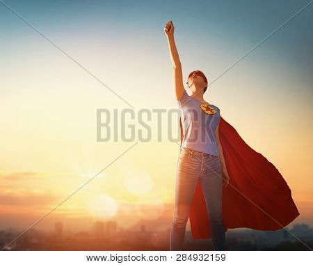 Joyful beautiful young woman in superhero costume posing on sunset background.