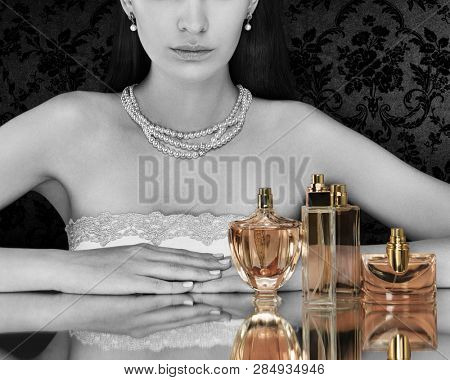 Beautiful woman and collection of perfumes bottles on dark background. Black and white. Tinted perfume bottles.