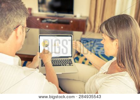 A man and a woman are working on a presentation on a laptop in the living room