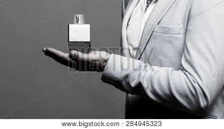 Masculine Perfume, Man In A Suit. Man Perfume, Fragrance. Male Holding Up Bottle Of Perfume. Perfume