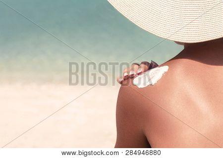 Woman Applying Sunscreen Creme On  Tanned  Shoulder. Skincare. Body Sun Protection Suncream. Bikini