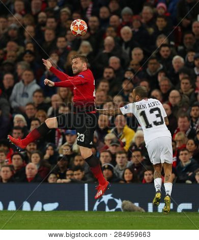 MANCHESTER, ENGLAND - FEBRUARY 12 2019: Luke Shaw of Manchester United and Dani Alves of PSG during the Champions League match between Manchester United and Paris Saint-Germain at Old Trafford Stadium