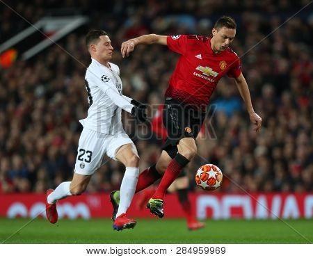 MANCHESTER, ENGLAND - FEBRUARY 12 2019: Julian Draxler of PSG and Nemanja Matic of Manchester United compete for the ball during the Champions League match between Manchester United and PSG