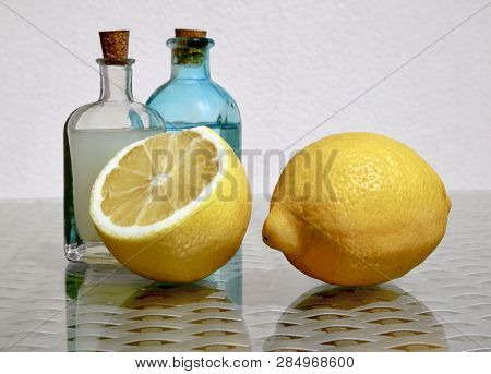 Still Life With Two Ripe Juicy Lemons And Cold Fresh Lemonade In Two Small Vintage Glass Botlles Aga