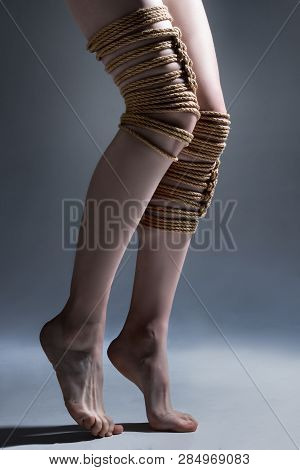 Young Seductive Slim Woman Lying On Mirror Floor Tied With Decorative Knots Of Natural Jute Rope. An