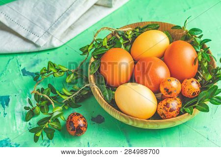 Easter Greeting Card With Colored Yellow Orange Eggs With Quail Eggs And Green Branches In Wooden Pl
