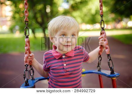 Cute Little Boy Having Fun On Outdoor Playground. Summer Active Sport Leisure For Kids. Child On Swi