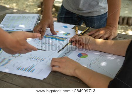 Business People Team Hands Pointing At Business Document On Financial Paper Data Charts During Discu