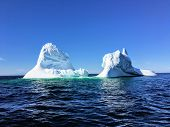A massive iceberg floating off the coast of Twilingate, Newfoundland and Labrador, Canada.  The iceberg floats in the vast open ocean and flowed down from the arctic. poster