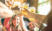 Friends drinking and toasting beer at brewery bar restaurant - Friendship concept on young millenial people having fun together on happy hour at brew pub - Focus on girl face - Summer sunshine filter poster