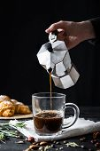 Pouring coffee from an italian percolator, shot in low key. Male hands pour black coffee from italian moka brewer poster