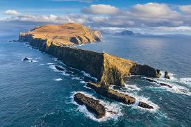 Aerial view of a lighthouse, dramatic cliffs and crashing waves along the island of Mykines in the Faroe Islands