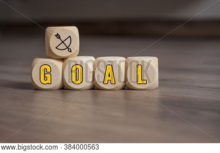 Cubes And Dice With Arrow And Bow Metaphor For Goal Or Target On Wooden Background