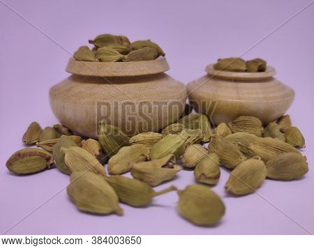 Whole Cardamon Seeds In Traditional Spice Pot. White Background.