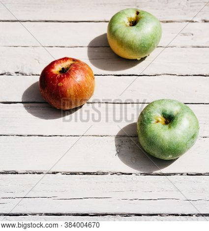One Red Apple And Two Green Apples Lie On A White Wooden Background. Fresh Apples In The Kitchen On