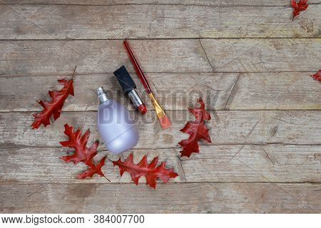 Perfume Bottle,lipstick,bruch On A Wooden Background With Autumn Red-orange Oak Leaves.women 's Acce