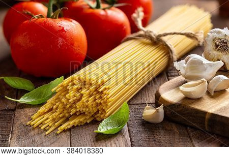 Closeup Of Raw Spaghetti Pasta Tied In A Bundle With Fresh Vine Tomatoes, Garlic And Basil On A Rust