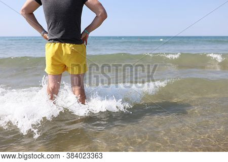 Lifeguard Man In Yellow Shorts Stands In Sea Water And Looks Into Distance. Rule Of Safe Behavior On