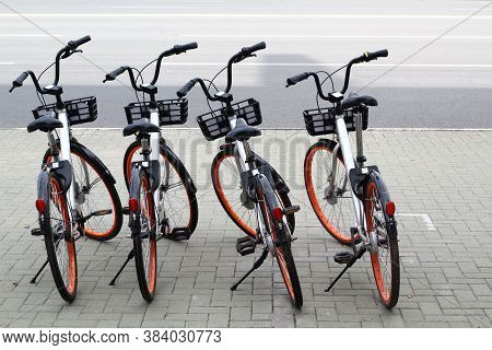 Bicycles Parked In Row At A Rent A Bike Shop On A Street. City Bike Public Rent Parking. Sharing Bik