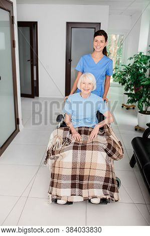An Elderly Woman Sitting In A Wheelchair Receives The Help Of A Nurse. Rehabilitation Of People Afte