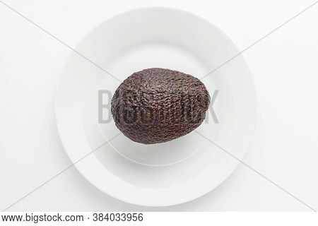 One Ripe Ready To Eat Avocado Fruit On A White Plate On A White Table