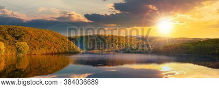 Mountain Lake Among The Forest At Sunset. Trees In Colorful Foliage. Beautiful Panorama In Autumn Ev