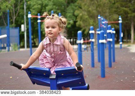 Baby Laughing Little Girl On Playground. Young Cute Sportswoman. Children's Playground Outdoor.