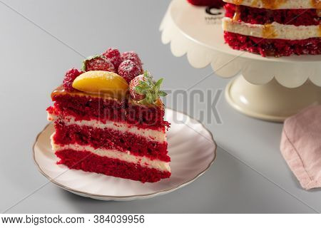Close-up Of A Slice Of Red Velvet Cake With Fresh Strawberries And Raspberries On The Table. Festive