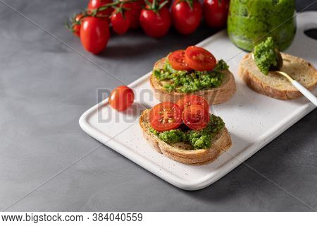 Fresh Made Antipasto With Green Basil Pesto And Cherry Tomatoes On A Dark Background. Traditional It