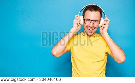 Portrait Of Happy Young Stylish Man In Yellow T-shirt, Glasses And Headphones Expressing Positivity
