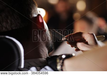 Client During Beard Shaving In Barber Shop. The Image Of A Straight Razor Shaving His Beard. Client