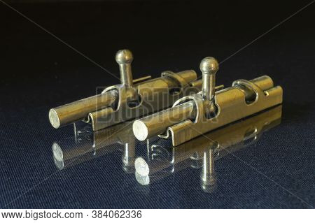 The Metallic Latch On Glass Table On Black Background. Bolt For Closing Door In Premises