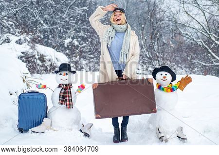 Planning Winter Vacations. Winter Holiday. Funny Woman And Snowmen With Suitcase
