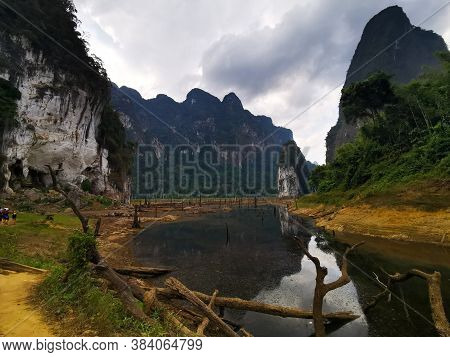 Stunning View With Lake And Dead Trees, Huge Karsts Mountains With Cloudy Sky