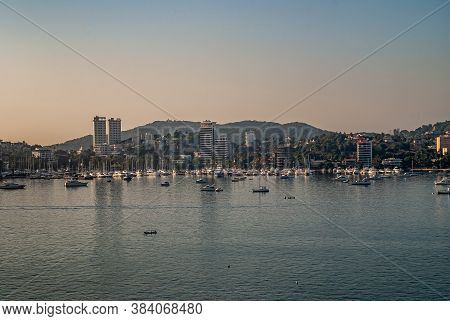 Acapulco, Mexico - November 25, 2008: Twilihgt Over The Blue Water Bay With Yacht Harbor And Highris