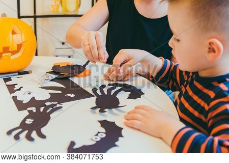 Young Mother With Toddler Son Making Craft Spiders For Halloween Holiday