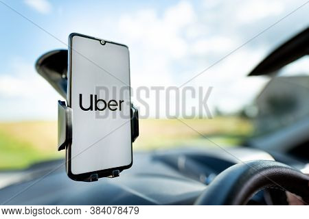 Wroclaw, Poland - Aug 25, 2020: Uber Driver Holding Smartphone In Car. Uber Is Sharing-economy Servi