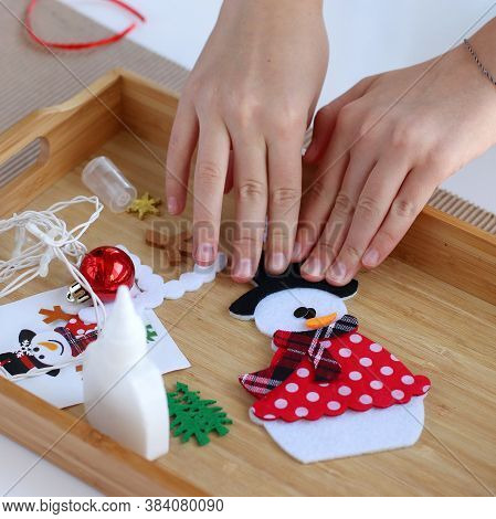 Getting Ready For Christmas. Childrens Hands Collect Christmas Tree Toy Snowman. Tools For Work Are