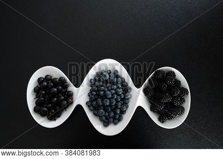 Set Of Different Types Of Black Berries In A White Plate On A Black Table. Stylish Seasonal Vitamins