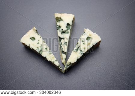 Three Triangles Of Roquefort Cheese With Mold On A Gray Background. Three Slices Of Blue Cheese