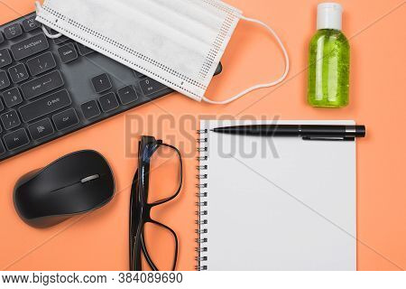 Back To Work. Empty Notepad, Computer Mouse, Keyboard, Eyeglasses, Antiseptic Hand Sanitizer And Fac