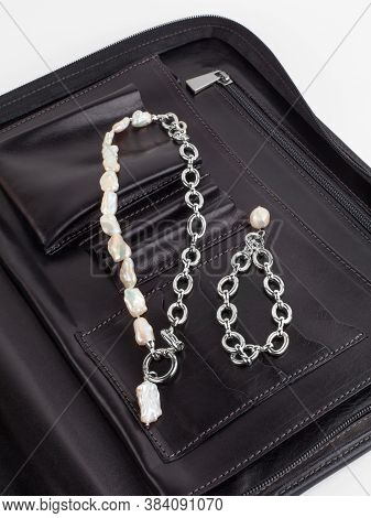 Women`s Baroque Pearl Necklace And Chain Bracelet With Pendant On Female Black Leather Cosmetic Bag.