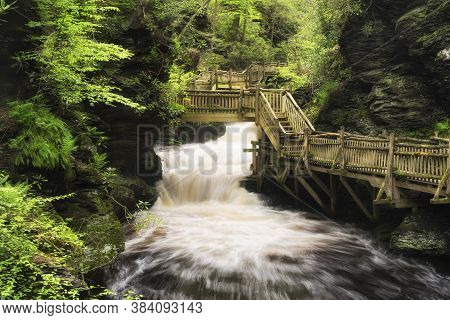 The Wooden Boardwalk Within The Bushkill Falls Scenic Area In Pennsylvania In Early Springtime.
