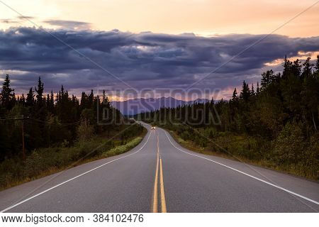 Beautiful View Of A Scenic Road, Alaska Hwy, In The Northern Rockies During A Dramatic Cloudy Sunset