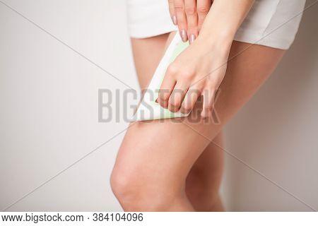 Beautician Waxing A Womans Leg Applying Wax Strip