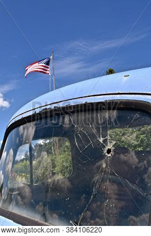 A Bullet Hole In An Old Truck Window  On The Drivers Side Shatters The Area With The American Flag F