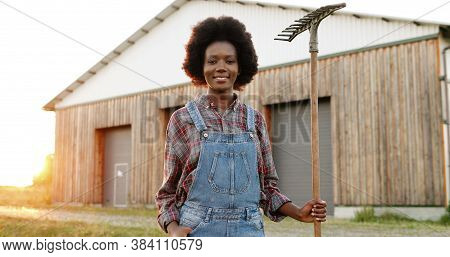 Portrait Of Beautiful African American Young Woman With Pitchfork Farmer Standing In Field At Shed O