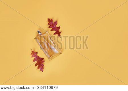 Eau De Toilette In A Transparent Bottle And Autumn Red Leaves Oak Lies Beautifully On A Yellow Backg